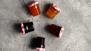 Top view of small glass jars filled with various sweet marmalade composed in circles on gray surface
