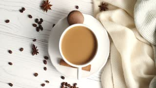 Top view of white ceramic mug with saucer filled with coffee and milk and served with macaron on table with soft fabric