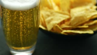 Transparent glass of light beer with foam and bowl of crispy golden nacho chips served on table