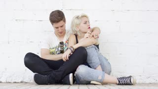 Trendy hipster young couple in love relaxing on a sidewalk leaning against a white wall in a close embrace enjoying a quiet moment