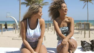Trendy multiethnic women sitting on waterfront of tropical coastline and sharing with news speaking in sunlight.