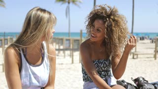 Trendy multiracial women sitting on waterfront in bright sunlight and chatting happily on background of beach and ocean.