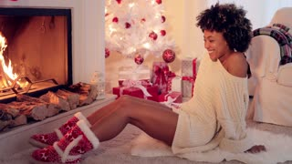 Trendy vivacious woman wearing Christmas booties warming her feet in front of a blazing fire as she sits on the floor alongside the tree and pile of gifts.