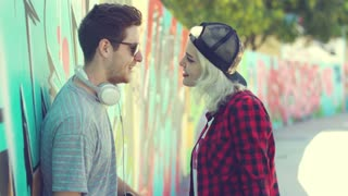 Trendy young couple with skateboards standing chatting in an urban street with a curving wall covered in colorful graffiti