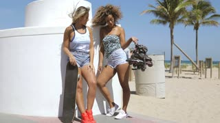 Trendy young multiethnic women in summer outfits posing with skateboard and rollers standing confidently on seafront.