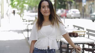 Trendy young woman standing in an urban street leaning on a restaurant table with a friendly happy smile and copy space