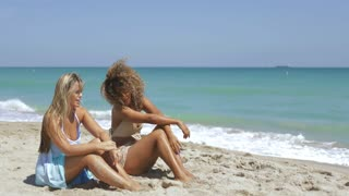 Two multiracial young women in beachwear sitting on sandy shoreline with blue ocean waves and enjoying sunlight.