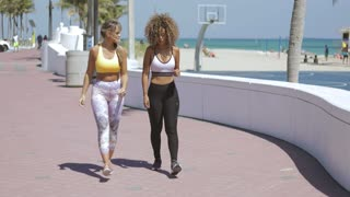 Two sportive multiethnic women in sportive clothing jogging in morning time on tropical seafront and chatting in process.