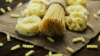 Uncooked macaroni of different sort placed on textile napkin on wooden background