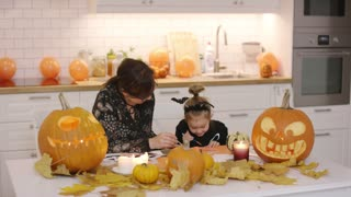Woman and her cute little daughter in Halloween costume sitting at table near jack-o-lanterns and leaves and painting Halloween decorations.