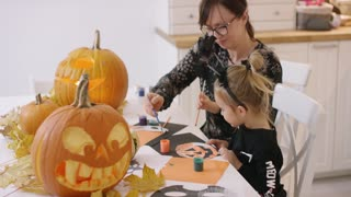 Woman in glasses and her daughter in Halloween costume sitting at table and painting jack-o-lantern made from paper.