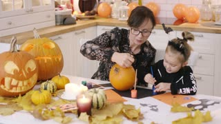 Woman in glasses and her little girl sitting at table in kitchen near Halloween decorations and painting face on small pumpkin.