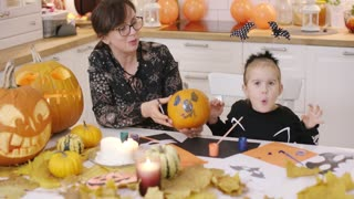 Woman in glasses holding pumpkin with painted face and little girl in cute Halloween costume trying to be scary.