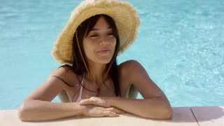 Woman in straw hat and swim suit stands in pool with elbows on the side while smiling to herself