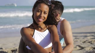 Wonderful laughing African-American girl in bikini sitting with man on sandy beach in tropical sunlight and smiling at camera.