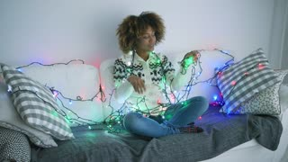 Wonderful romantic model in warm knitted sweater posing on sofa at home all tangled in glowing garland shining with different lights.