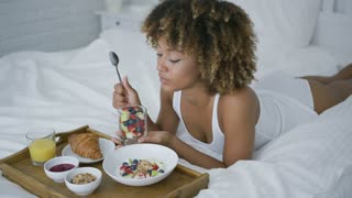 Wonderful young model lying on cozy bed in morning time holding glass of fruit for breakfast and looking dreamily and contently.