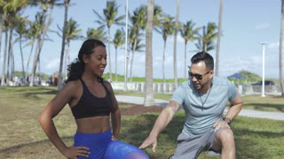 Young African-American woman in sportswear working out under control of man in tropical park enjoying training.
