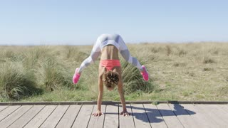 Young African woman standing on hands on the pavement while doing yoga in Tarifa beach.