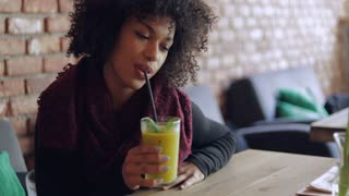 Young African woman with short curly hair drinking smoothie with straw while sitting at table in cafe and looking away.