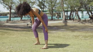 Young anonymous black girl in sportswear bending forward stretching spine standing on meadow in sunny park.