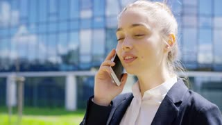 Young attractive female wearing formal clothing and talking phone on background of cityscape in summer.