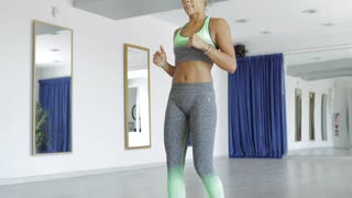 Young attractive woman in sportswear working out hard and stretching leg while bending in dance class.