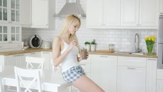 Young beautiful fit woman in home clothing eating chocolate spread from jar in modern light kitchen.
