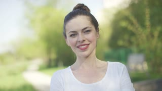 Young beautiful woman in white t-shirt smiling and looking at camera on blurred green background