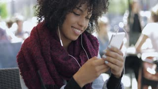 Young black woman in casual clothing looking content while using smartphone and headphones and sitting in outside cafe.