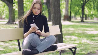 Young casual female sitting on bench with legs crossed and holding smartphone while listening to music with headphones