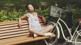 Young casual woman sitting with legs crossed and eyes closed on wooden bench in park with bicycle near and enjoying sunlight.