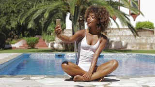 Young charming ethnic model in white swimming suit sitting on side of pool using smartphone and posing for selfie in sunlight.
