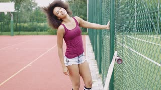 Young charming woman in summer clothing posing on sports ground near metal fence with longboard near and smiling at camera.