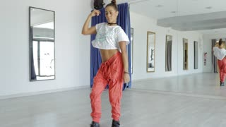 Young confident woman in casual clothing posing and showing new dance while training alone in studio on background of mirror.