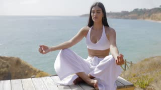 Young confident woman in white posing on wooden viewpoint and meditating with eyes closed on background of ocean and tropics.