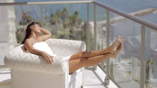 Young content woman in white towel sitting in comfortable armchair and enjoying tropical sun while relaxing on balcony of luxurious hotel.