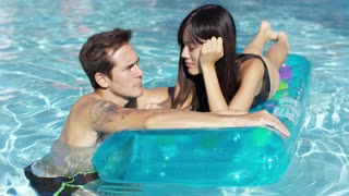 Young couple in love relaxing in the pool with the smiling young woman floating on an inflatable bed grinning at the man in the water