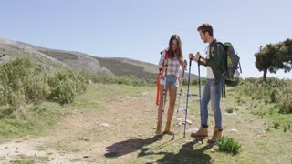 Young couple with backpack hiking in mountains and standing on road under sun light.