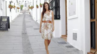 Young elegant girl in summer dress walking down street city in bright sunlight looking around and enjoying traveling.
