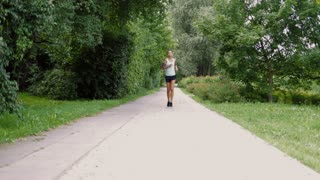Young ethnic cheerful woman in sportswear listening to music with smartphone and running in summer park smiling at camera.