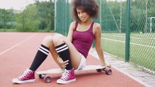 Young ethnic girl in trendy sportive clothing posing coquettishly on longboard and looking at camera on background of basketball ground.