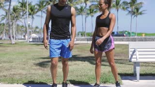 Young ethnic man and woman standing and interacting while doing fitness on green lawn in sunny park.