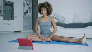 Young ethnic model in sportswear sitting on mat at home practicing yoga and watching tutorial on tablet looking concentrated.
