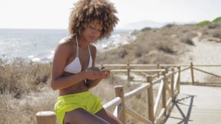 Young ethnic model in swimsuit and shorts relaxing on coastal pier and browsing smartphone on background of ocean in bright sunlight.