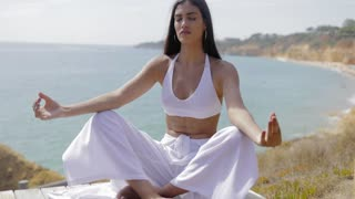 Young ethnic model in white outfit relaxing and meditating with eyes closed sitting on shoreline with background of ocean in tropical sunlight.