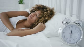 Young ethnic model lying on comfortable bed looking content while alarm clock ringing on small table near awakening.