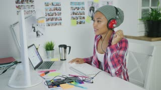 Young ethnic woman wearing hat and listening to music with headphones posing at table in office working on new project and watching computer.