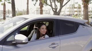 Young excited girl driving car and greeting someone at street waving with hand in bright sunlight looking away on background of tropical resort.