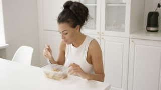 Young female in home clothing sitting at table in modern and light kitchen eating food from container.